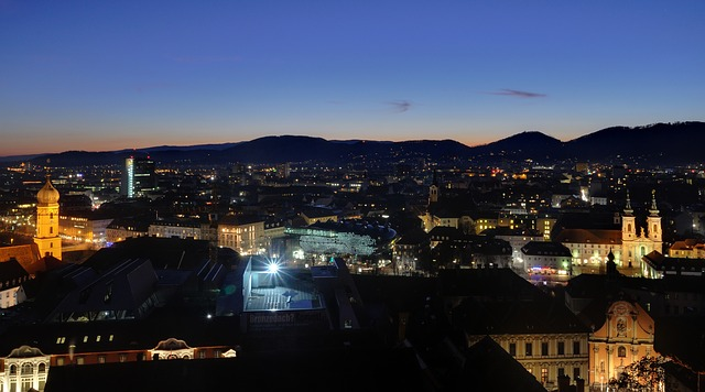 Graz via https://pixabay.com/en/graz-austria-mountains-night-83349/